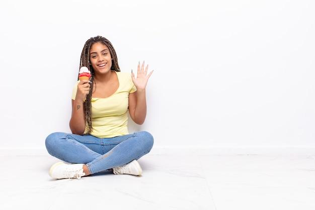 Młoda afro kobieta uśmiecha się radośnie i wesoło, macha ręką, wita i wita lub żegna się. koncepcja lodów