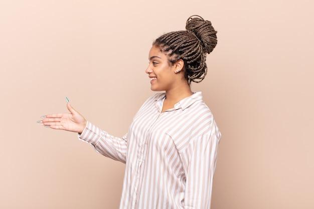 Młoda afro kobieta uśmiecha się, wita cię i oferuje uścisk dłoni, aby sfinalizować udaną transakcję