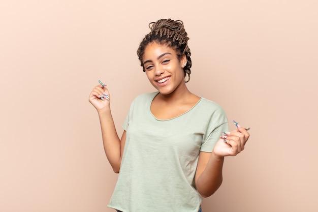 Młoda afro kobieta uśmiechnięta, beztroska, zrelaksowana i szczęśliwa, tańcząca i słuchająca muzyki, bawiąca się na imprezie