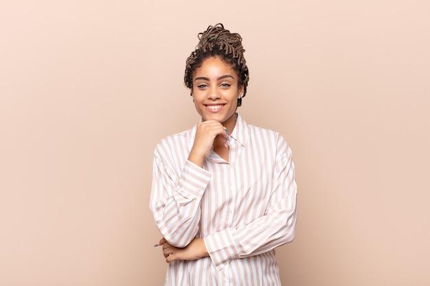 Młoda afro kobieta uśmiechnięta, ciesząca się życiem, szczęśliwa, przyjazna, zadowolona i beztroska z ręką na brodzie