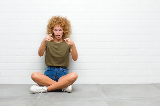 Młoda afro kobieta wskazująca do przodu dwoma palcami i gniewnym wyrazem twarzy, mówiąca, że masz wykonywać swoje obowiązki siedząc na podłodze