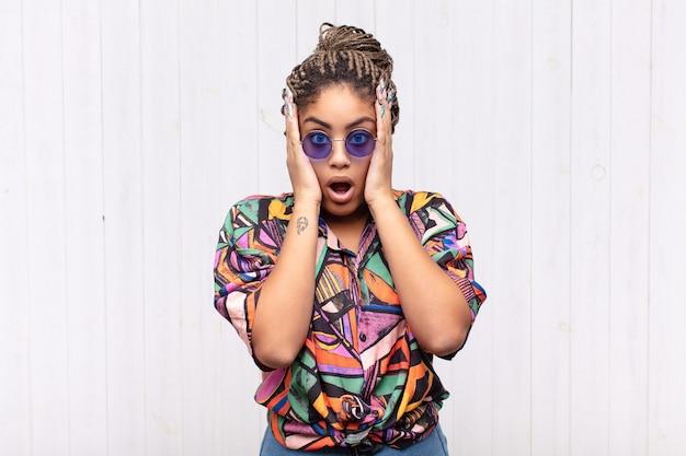Młoda afro kobieta wyglądająca na nieprzyjemnie zszokowaną, przestraszoną lub zmartwioną, z szeroko otwartymi ustami i zakrywającymi uszy dłońmi
