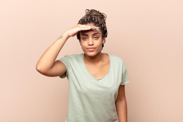 Młoda afro kobieta wyglądająca na oszołomioną i zdumioną, z ręką na czole spoglądającą w dal, obserwującą lub poszukującą