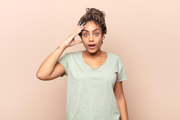Młoda afro kobieta wyglądająca na szczęśliwą, zdziwioną i zaskoczoną, uśmiechniętą i uświadamiającą sobie niesamowite i niewiarygodnie dobre wieści