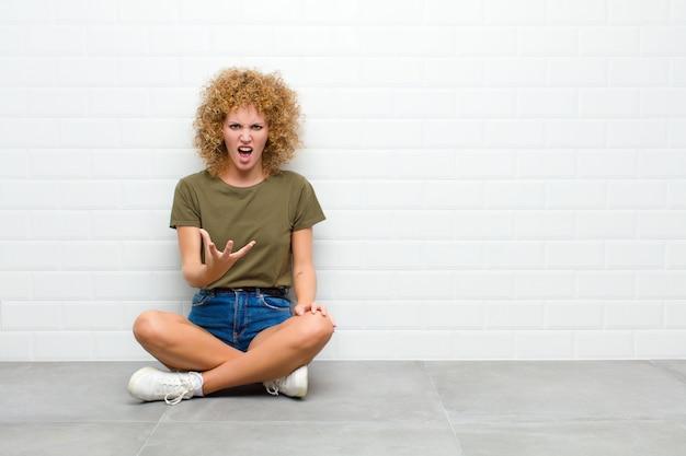 Młoda afro kobieta wyglądająca na wściekłą, zirytowaną i sfrustrowaną krzyczącą wtf lub co jest nie tak z tobą siedzącym na podłodze