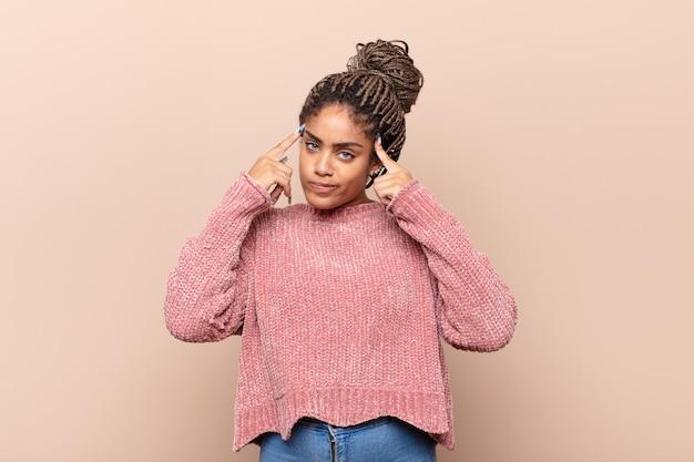 Młoda afro kobieta wyglądająca na zdziwioną i zdezorientowaną, przygryzając wargę nerwowym gestem, nie znając odpowiedzi na problem