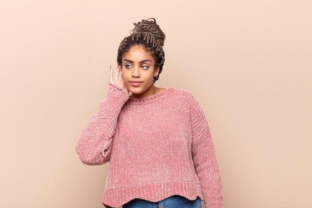 Młoda afro kobieta wyglądająca poważnie i zaciekawiona, słuchająca, próbująca usłyszeć tajną rozmowę lub plotkę, podsłuchująca
