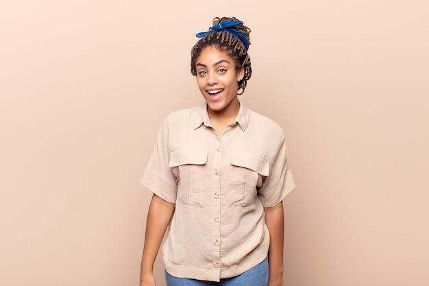 Młoda afro kobieta z dużym, przyjaznym, beztroskim uśmiechem, pozytywnie wyglądająca, zrelaksowana i szczęśliwa