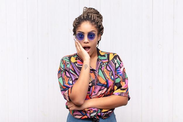 Młoda afro kobieta z otwartymi ustami w szoku i niedowierzaniu, z dłonią na policzku i skrzyżowanymi rękami, oszołomiona i zdumiona