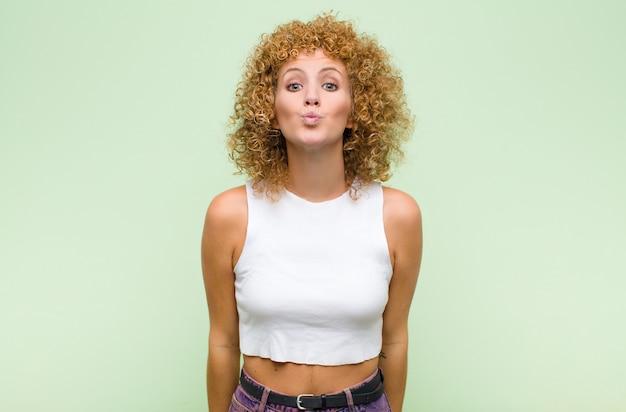 Młoda afro kobieta zaciskająca usta wraz z uroczym, wesołym, radosnym i uroczym wyrazem twarzy, wysyłająca buziaka na zieloną ścianę