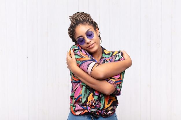 Młoda afro kobieta zakochana, uśmiechnięta, przytulająca się i przytulająca, pozostająca samotna, samolubna i egocentryczna