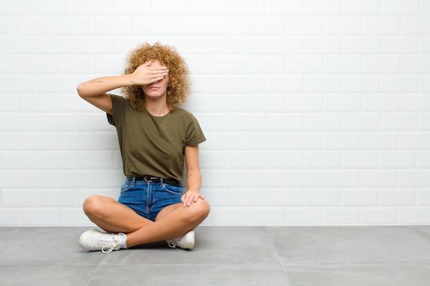 Młoda afro kobieta zakrywająca oczy jedną ręką, czująca się przestraszona lub niespokojna, zastanawiająca się lub na ślepo czekająca na niespodziankę siedząca na podłodze