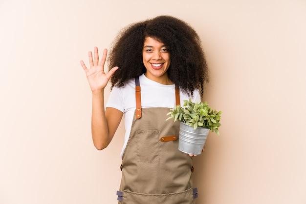 Młoda afro ogrodniczka kobieta trzyma rośliny isolatedsmiling wesoły seans liczba pięć z palcami.
