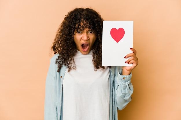 Młoda afroamerykanin afro kobieta trzyma kartę walentynki krzycząc bardzo zły i agresywny.