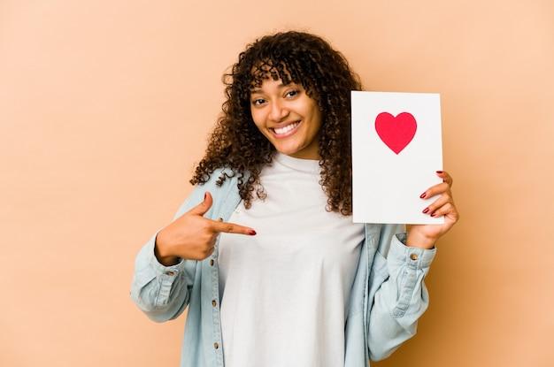 Młoda afroamerykanin afro kobieta trzyma kartę walentynki osoba, wskazując ręką na przestrzeni kopii koszuli, dumny i pewny siebie