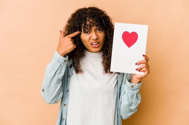 Młoda afroamerykanin afro kobieta trzyma kartę walentynki pokazując gest rozczarowania z palcem wskazującym.