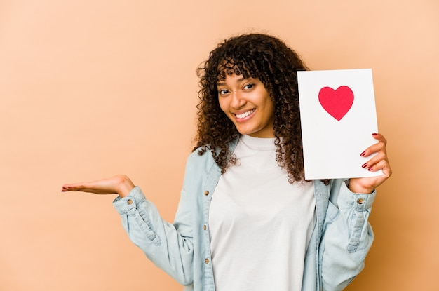 Młoda afroamerykanin afro kobieta trzyma kartę walentynki pokazując miejsce na kopię na dłoni i trzymając drugą rękę na talii.