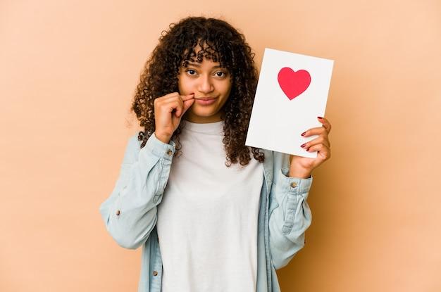 Młoda afroamerykanin afro kobieta trzyma kartę walentynki z palcami na ustach, zachowując tajemnicę.