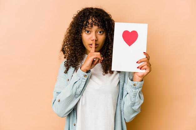 Młoda afroamerykanin afro kobieta trzyma kartę walentynkową zachowując tajemnicę lub prosząc o ciszę.