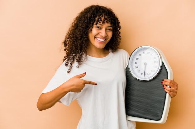 Młoda afroamerykanin afro kobieta trzyma osobę skali, wskazując ręką na przestrzeni kopii koszuli, dumny i pewny siebie