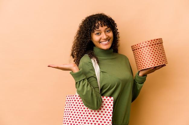 Młoda afroamerykanin afro kobieta trzyma prezent na walentynki pokazując miejsce na kopię na dłoni i trzymając drugą rękę na talii.