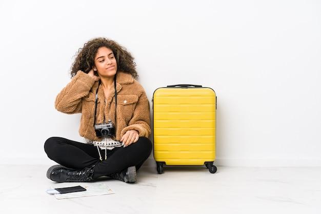 Młoda afroamerykanin kobieta gotowa do podróży, dotykając tyłu głowy, myśląc i dokonując wyboru.