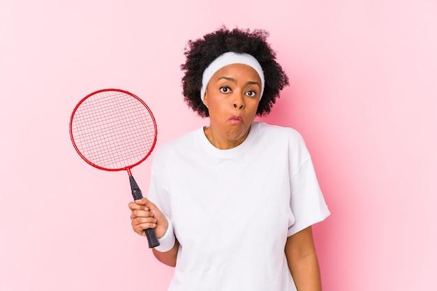 Młoda afroamerykanin kobieta gra w badmintona na białym tle wzrusza ramionami i zdezorientowany otwartymi oczami.