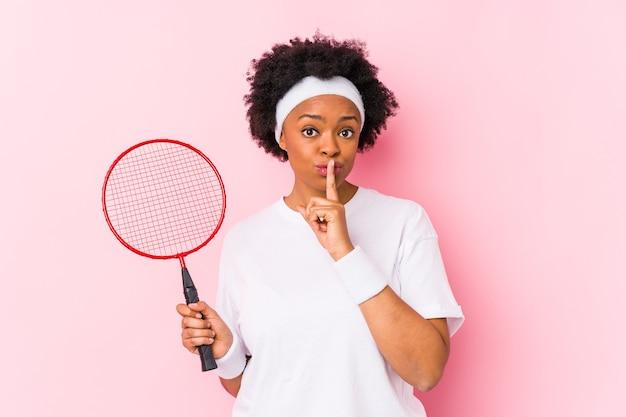 Młoda afroamerykanin kobieta gra w badmintona na białym tle, zachowując tajemnicę lub prosząc o ciszę.