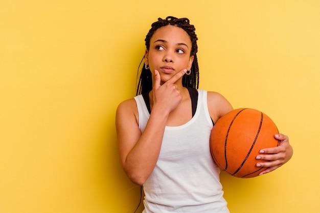 Młoda afroamerykanin kobieta gra w koszykówkę na białym tle na żółtej ścianie, patrząc w bok z wyrazem wątpliwości i sceptycyzmu