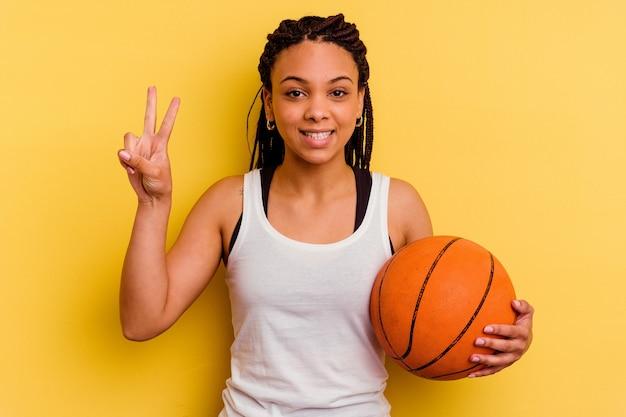 Młoda afroamerykanin kobieta gra w koszykówkę na białym tle na żółtej ścianie pokazuje numer dwa palcami