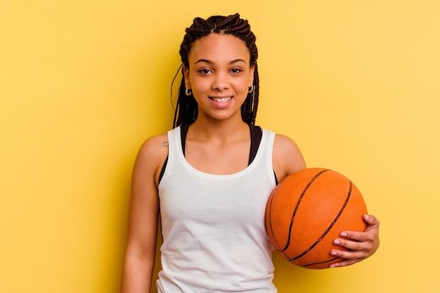 Młoda afroamerykanin kobieta gra w koszykówkę na białym tle na żółtym tle szczęśliwa, uśmiechnięta i wesoła.