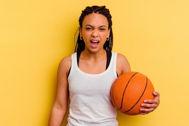 Młoda afroamerykanin kobieta gra w koszykówkę na żółtym tle krzyczy bardzo zły i agresywny.