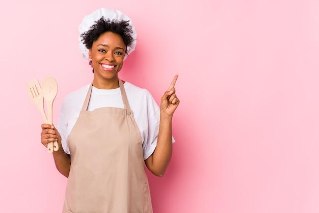Młoda afroamerykanin kobieta kucharz uśmiecha się i wskazuje na bok, pokazując coś w puste miejsce.