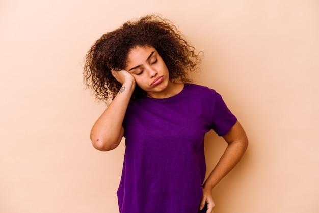 Młoda afroamerykanin kobieta na beżowej ścianie, która jest znudzona, zmęczona i potrzebuje dnia relaksu.