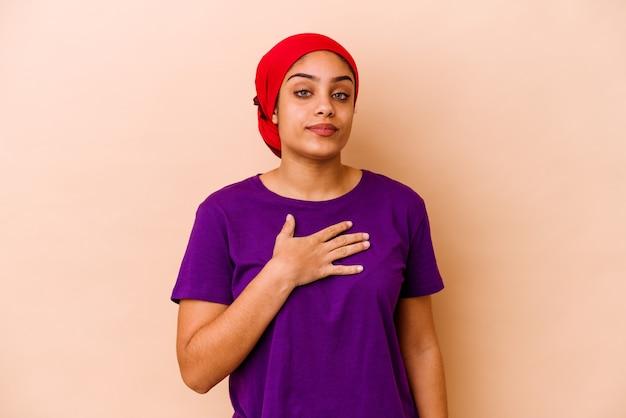 Młoda afroamerykanin kobieta na beżowym składaniu przysięgi, kładąc rękę na piersi.