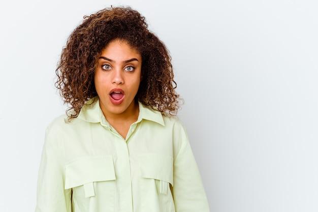 Młoda afroamerykanin kobieta na białej ścianie jest w szoku z powodu czegoś, co widziała.
