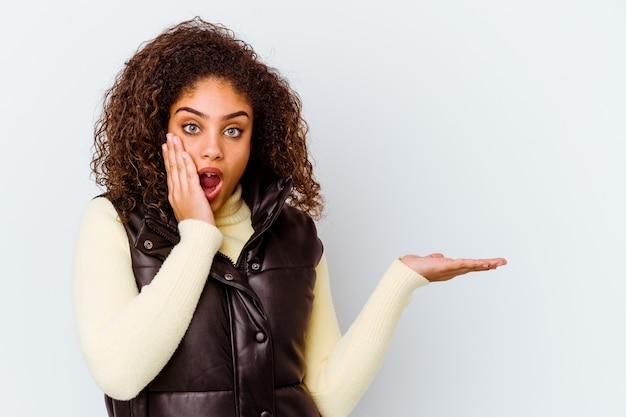 Młoda afroamerykanin kobieta na białej ścianie pod wrażeniem, trzymając miejsce na dłoni.