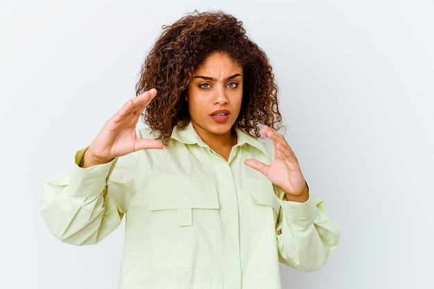 Młoda afroamerykanin kobieta na białej ścianie trzyma coś z palmami
