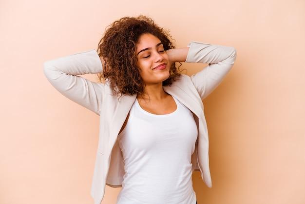 Młoda afroamerykanin kobieta na białym tle na beżowej ścianie cierpi na ból szyi z powodu siedzącego trybu życia