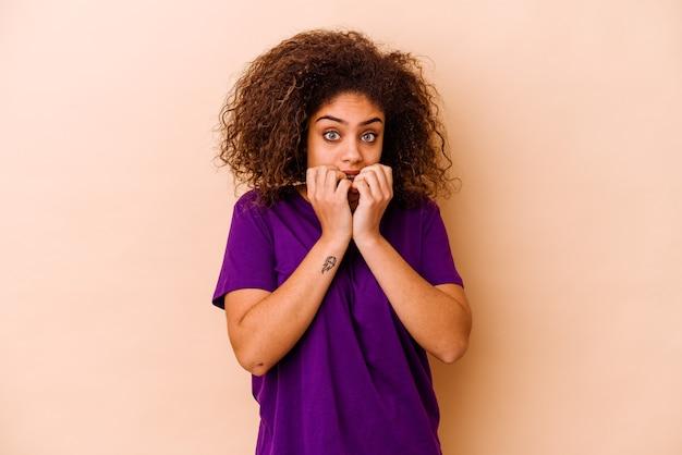 Młoda afroamerykanin kobieta na białym tle na beżowej ścianie gryzie paznokcie, nerwowa i bardzo niespokojna