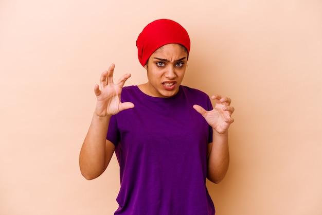 Młoda afroamerykanin kobieta na białym tle na beżowej ścianie pokazując pazury imitujące kota, agresywny gest.