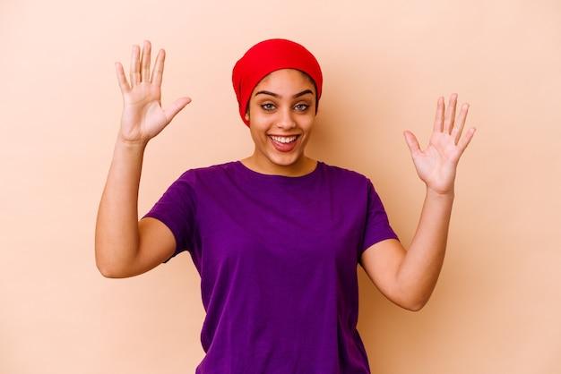 Młoda afroamerykanin kobieta na białym tle na beżowej ścianie świętuje zwycięstwo lub sukces, jest zaskoczony i zszokowany.
