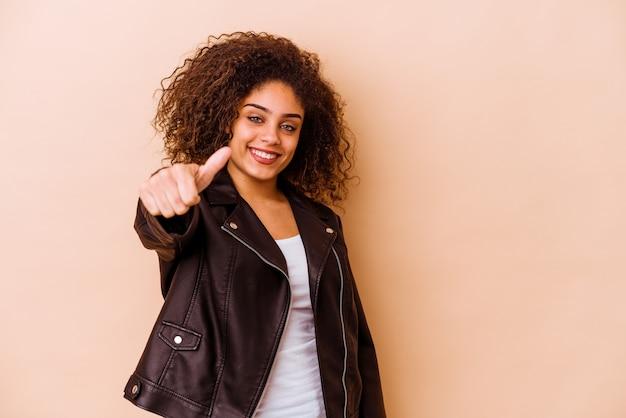 Młoda afroamerykanin kobieta na białym tle na beżowej ścianie, uśmiechając się i podnosząc kciuk do góry