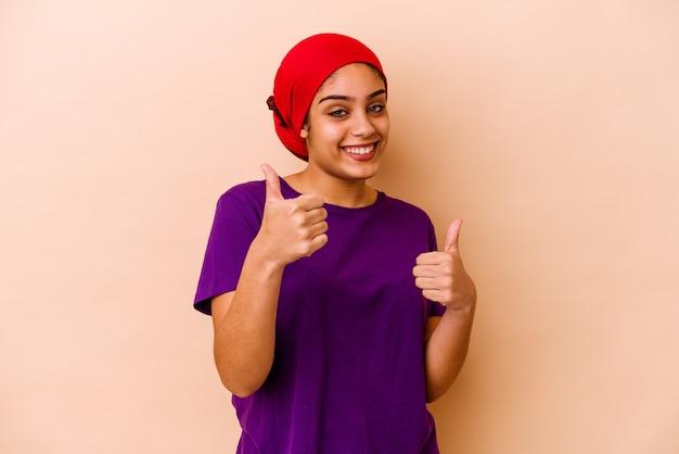 Młoda afroamerykanin kobieta na białym tle na beżowym tle, podnosząc kciuki do góry, uśmiechnięta i pewna siebie.