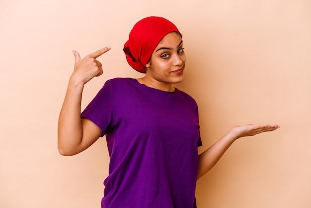 Młoda afroamerykanin kobieta na białym tle na beżowym tle trzymając i pokazując produkt pod ręką.