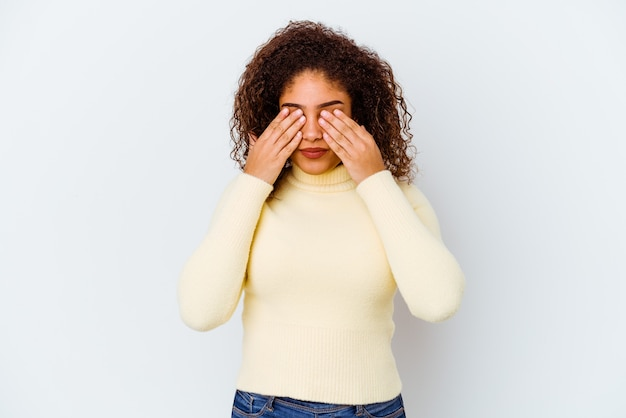 Młoda afroamerykanin kobieta na białym tle na białej ścianie boi się obejmujących oczy rękami.