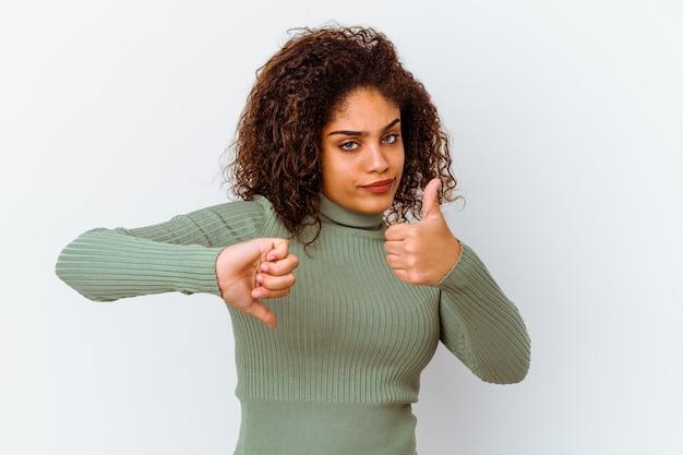 Młoda afroamerykanin kobieta na białym tle na białej ścianie pokazuje kciuk w górę i w dół, trudno wybrać koncepcję