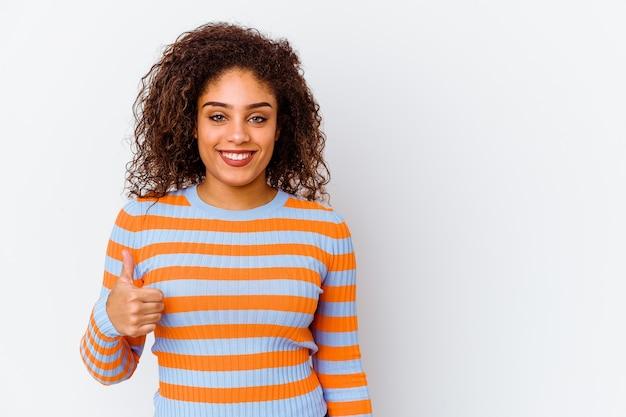 Młoda afroamerykanin kobieta na białym tle na białej ścianie, uśmiechając się i podnosząc kciuk