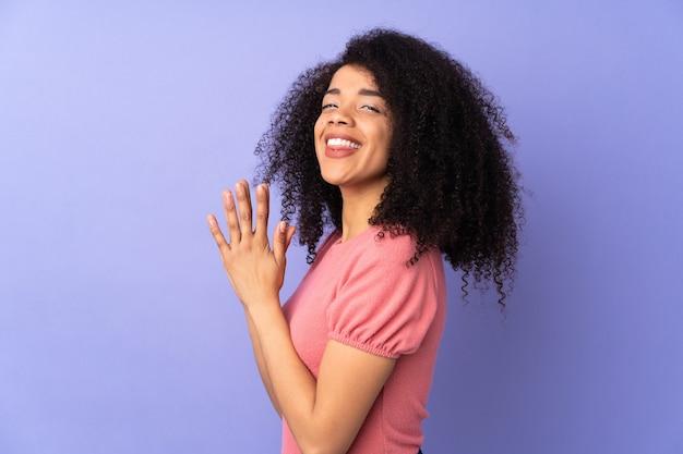 Młoda afroamerykanin kobieta na białym tle na fioletowy coś knuje