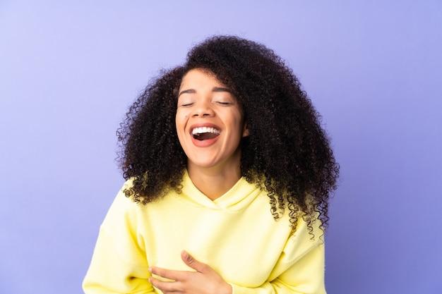 Młoda afroamerykanin kobieta na białym tle na fioletowy dużo uśmiecha się
